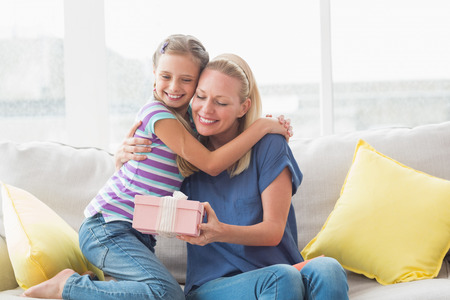 madre: Retrato de la madre feliz con la hija abarcamiento de regalos en casa