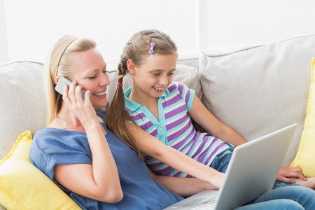 Happy mother and daughter using technologies on sofa in living room photo