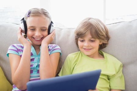 girl notebook: Happy boy playing music on laptop for sister in living room Stock Photo