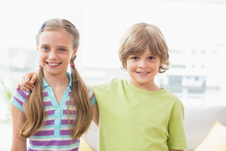 arm around: Portrait of happy siblings standing arm around at home Stock Photo