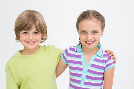 arm around: Portrait of cute siblings standing arm around on white background Stock Photo