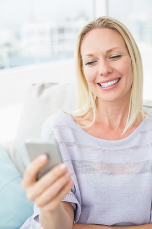 text room: Smiling woman text messaging through smart phone in living room