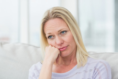 Upset woman with hand on chin sitting in living room