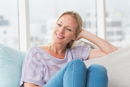 Relaxed woman looking away while sitting on sofa at home