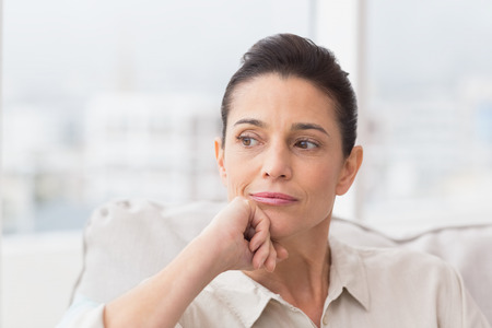 thinking people: Thoughtful woman sitting on sofa in living room Stock Photo