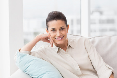 confortable: Portrait of happy woman relaxing on sofa in living room