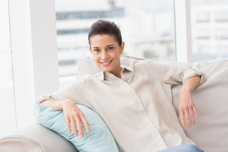 confortable: Portrait of happy woman sitting comfortably on sofa in living room Stock Photo