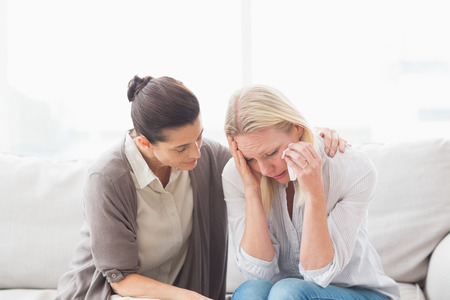 health woman: Patient crying next to her therapist while she is comforting her