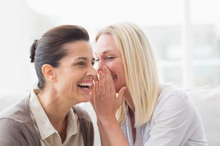 女性の笑顔とソファの上に座っている彼女の友人に秘密を明らかに