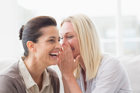 mature women: Woman revealing secret to her friend smiling and sitting on sofa