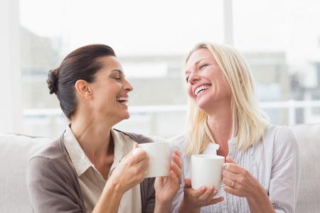 přátelé: Veselé ženy klábosení zároveň s kávou v obývacím pokoji