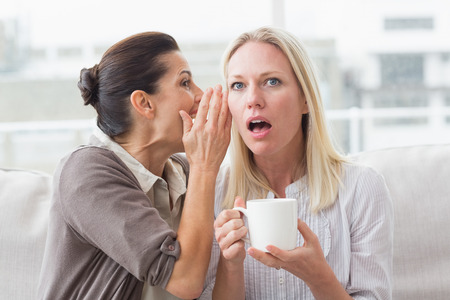 secret: Woman revealing secret to her surprised friend and sitting on sofa