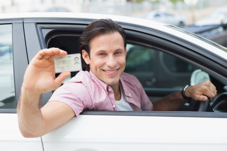 new driver: Man smiling and holding his driving license in his car Stock Photo