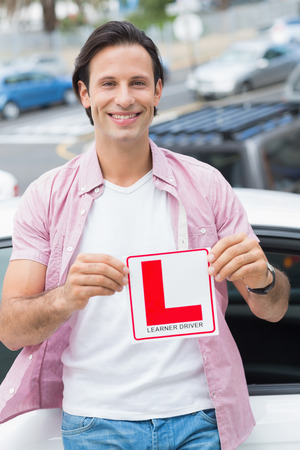 l plate: Learner driver smiling and holding l plate in front of his car