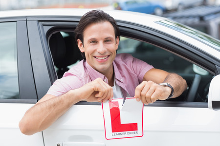 l plate: Learner driver smiling and tearing l plate in his car Stock Photo