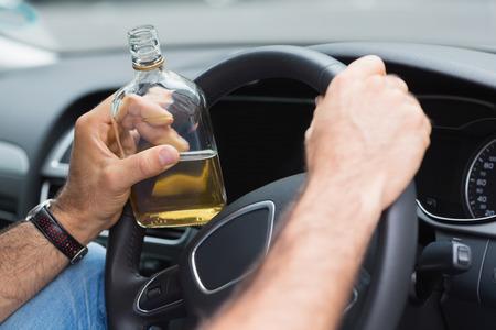 hombre manejando: Hombre bebiendo alcohol mientras se conduce en su coche