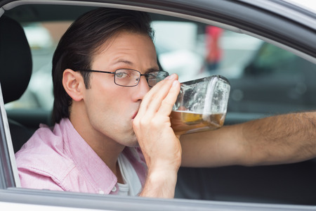 intoxicated: Man drinking alcohol while driving in his car