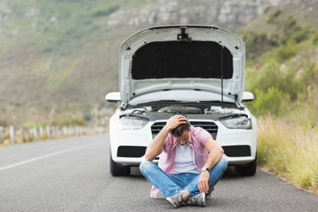 Stressed man sitting after a car breakdown at the side of the road Reklamní fotografie