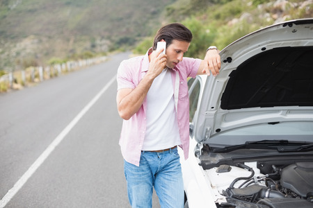 breakdown: Man after a car breakdown at the side of the road Stock Photo