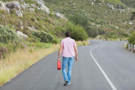 walking away: Man walking away holding petrolcan at the side of the road