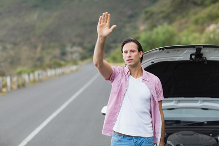 apprehensive: Man waving after a breakdown at the side of the road Stock Photo