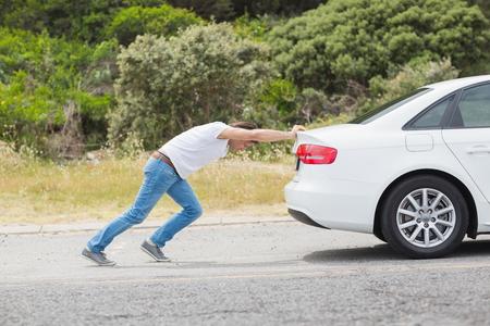 길가에서 그의 차를 밀고하는 남자