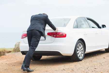 Businessman pushing his car at the side of the road