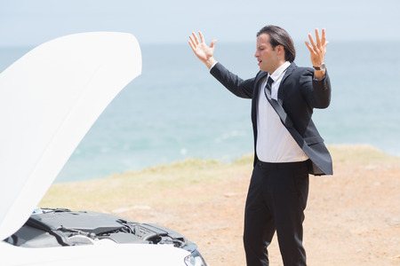 road rage: Anger businessman looking at engine of his car Stock Photo