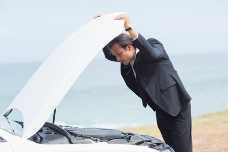 engine bonnet: Stressed businessman looking at engine of his car Stock Photo