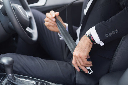 seat belt: Businessman putting on his seat belt in his car Stock Photo