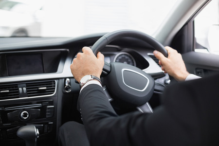 drivers seat: Businessman in the drivers seat in his car
