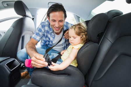cars road: Father securing baby in the car seat in his car Stock Photo