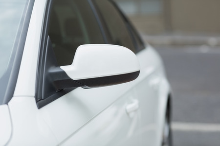 hubcap: Close up of a wing mirror of white car