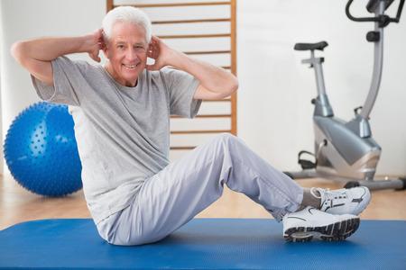 active retirement: Senior man training in fitness studio