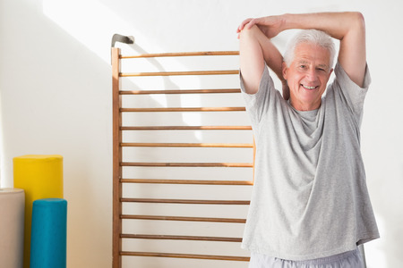 man arm: Senior man stretching in fitness studio