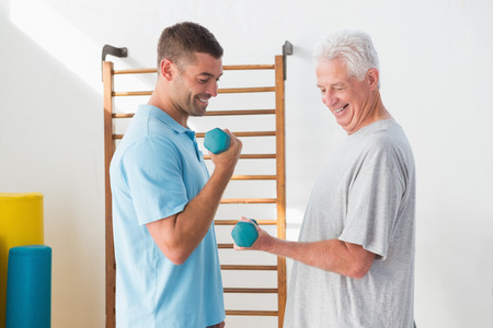 instructing: Senior man training with his coach in fitness studio