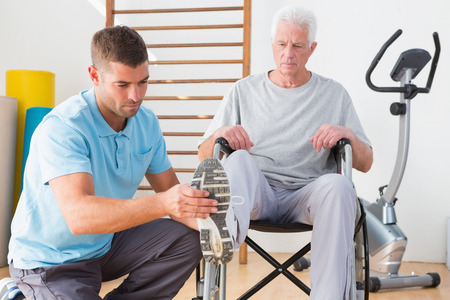 Coach helping invalid senior in fitness studio Stock Photo