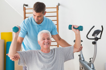 man working out: Senior man working out with his trainer in fitness studio