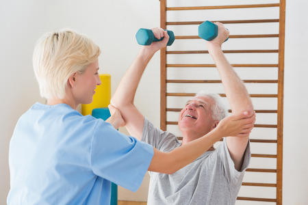 man working out: Senior man working out with his therapist in fitness studio Stock Photo