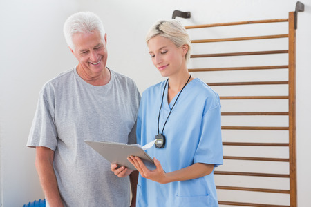 convalescence: Therapist showing clipboard to senior man in fitness studio
