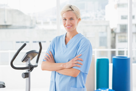 physical: Smiling therapist with arms crossed in fitness studio