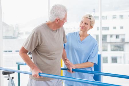 ayudando: Hombre mayor que recorre con el terapeuta ayuda en el estudio de fitness