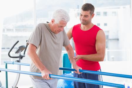 aide à la personne: Senior homme marchant avec l'entraîneur de l'aide dans le studio de remise en forme Banque d'images