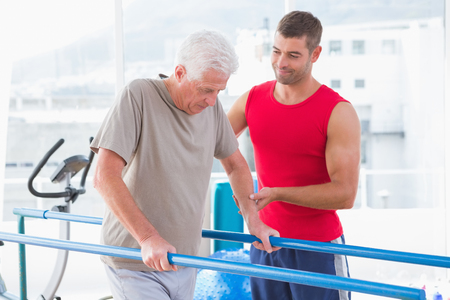 personal training: Senior man walking with coach help in fitness studio