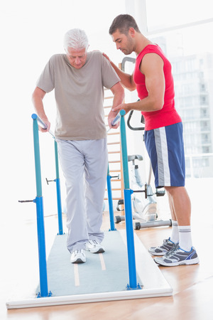 convalescence: Senior man walking with coach help in fitness studio