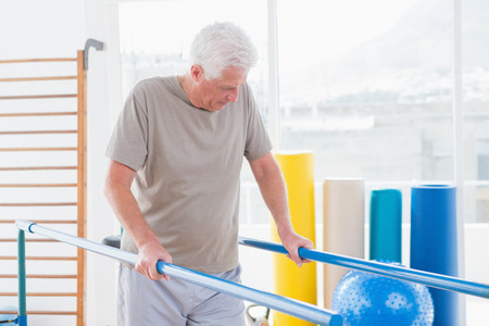 convalescence: Senior man walking with parallel bars in fitness studio Stock Photo