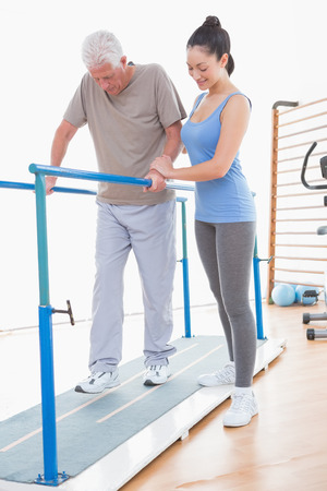 physical injury: Senior man walking with parallel bars and coach help in fitness studio