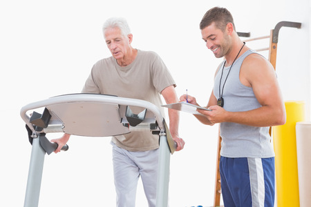 convalescence: Senior man on treadmill with trainer in fitness studio Stock Photo