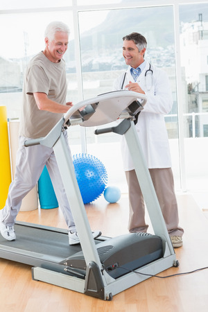 senior exercise: Senior man on treadmill with therapist in fitness studio