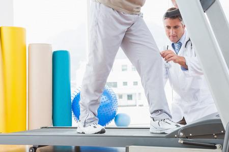fisico: Hombre mayor en la rueda de ardilla con el terapeuta en cuclillas en el estudio de fitness Foto de archivo